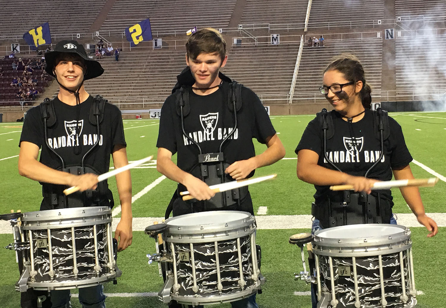Drumline members play in front of the student section during a home game at Kimbrough Stadium.