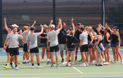 The varsity tennis team celebrates after a district win. The team will begin playoffs Oct. 14.