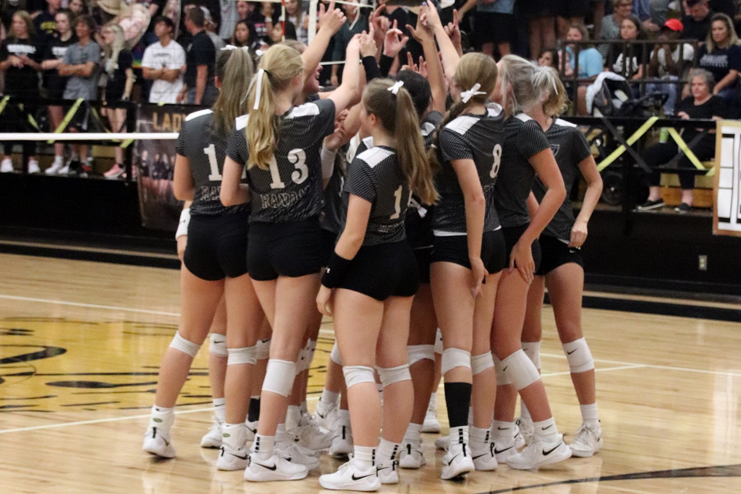 The varsity volleyball team huddles together during the Sept. 24 match.