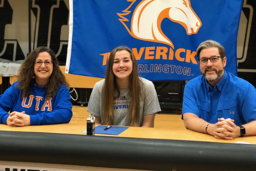 With her parents, senior Brianna Ford signs her letter of intent to play volleyball for the University of Texas at Arlington.