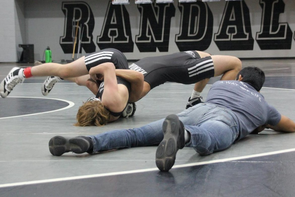 Coach David Quirino officiates while Randall wrestlers compete for a spot on varsity.