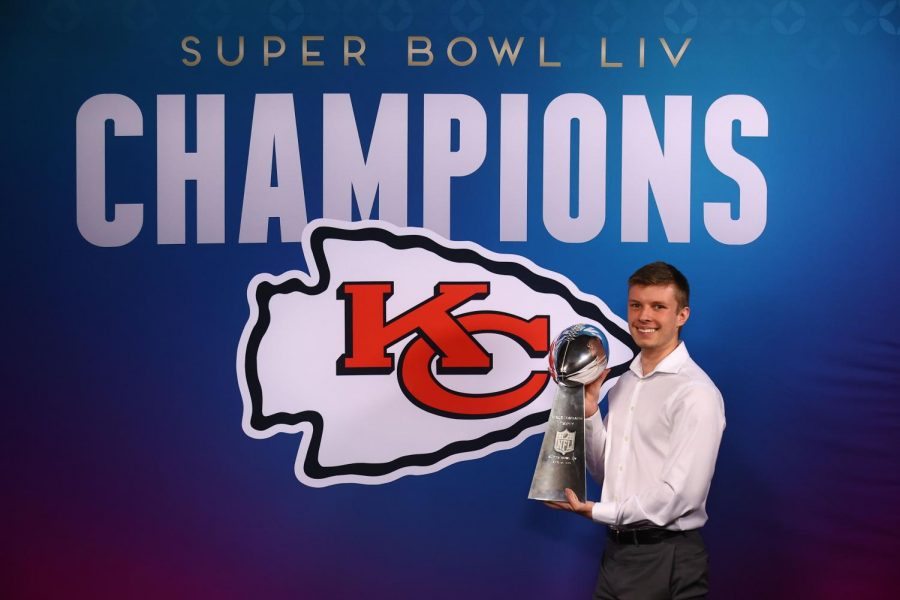 Ryan Larson poses with the Kansas City Chiefs' Super Bowl Championship trophy.