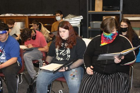Choir students practice sheet music in choir.