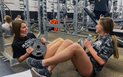 Juniors Addy Reilly and Kylee Williams have a conversation while completing their ab workout.