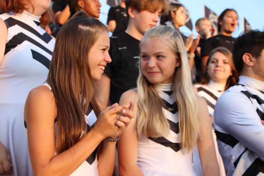 Color Guard members Hailey Roberson and Alexiah Ferril enjoy the Friday night game.